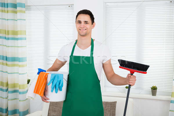 Happy Man In Green Apron Holding Cleaning Equipment At Home Stock photo © AndreyPopov