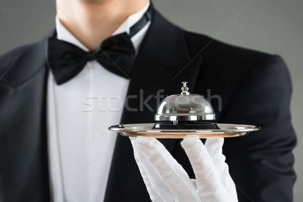 Midsection Of Waiter Holding Service Bell In Plate Stock photo © AndreyPopov