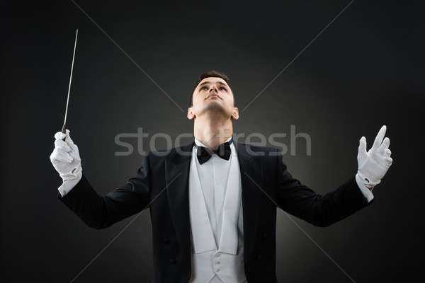 Music Conductor Looking Up While Holding Baton Stock photo © AndreyPopov