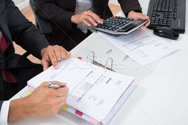 Close-up Of Two Businesspeople Calculating Invoice Stock photo © AndreyPopov