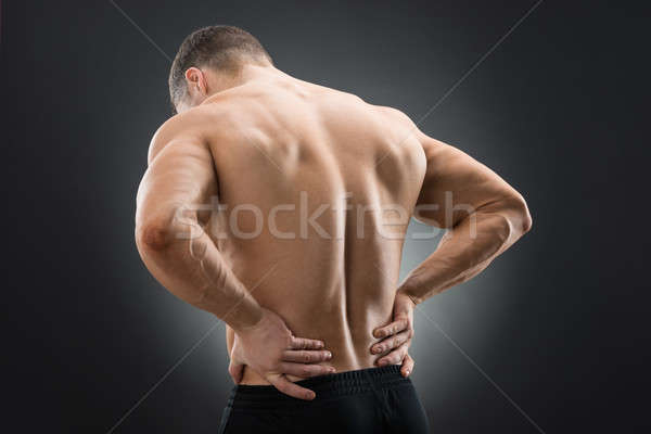 Rear View Of Muscular Man Suffering From Backache Stock photo © AndreyPopov