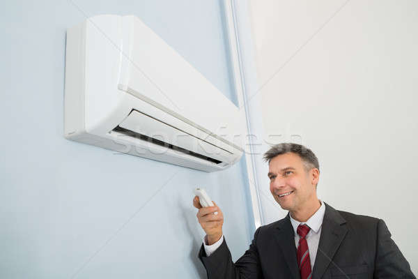 Businessman Using Remote Control To Operate Air Conditioner Stock photo © AndreyPopov