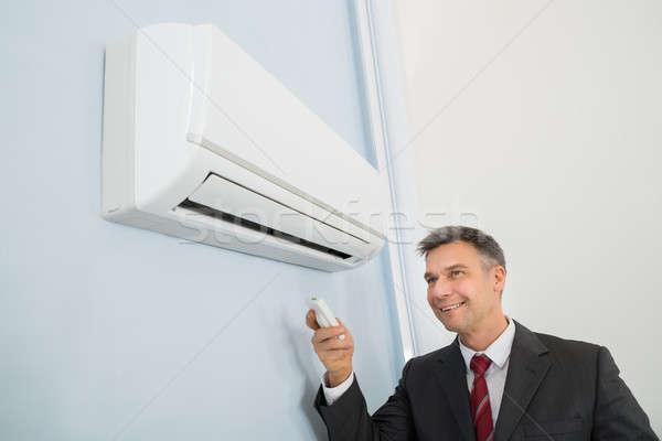 Imprenditore telecomando condizionatore d'aria maturo felice muro Foto d'archivio © AndreyPopov