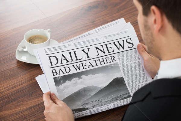 Businessman Reading Weather News On Newspaper Stock photo © AndreyPopov