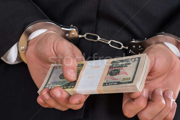 Stock photo: Businessman In Handcuffs Holding Dollars