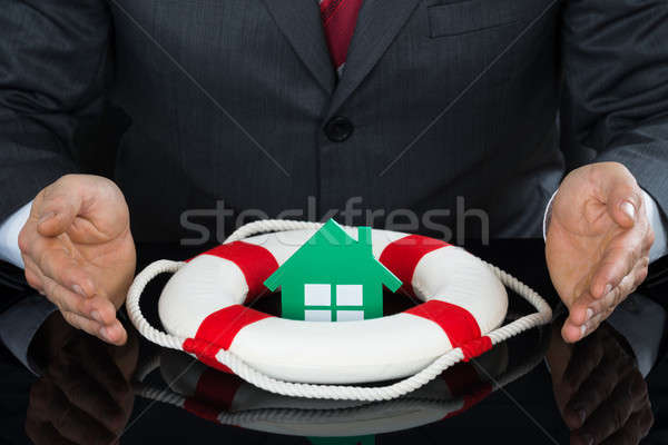 Close-up Of Businessman Hand Sheltering House With Lifebuoy Stock photo © AndreyPopov