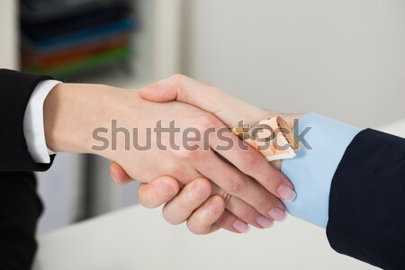 Businessperson Bribing Partner While Shaking Hand Stock photo © AndreyPopov