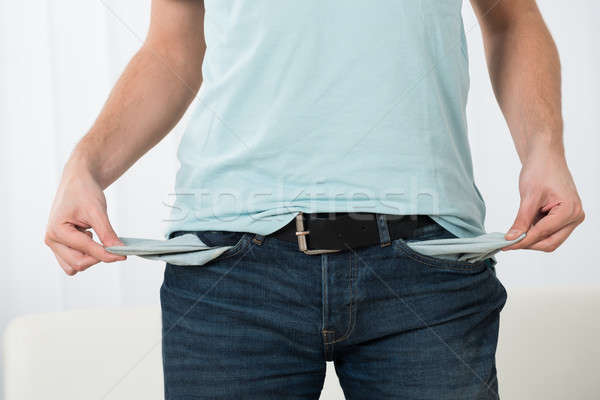 Young Man Showing Empty Pockets Stock photo © AndreyPopov