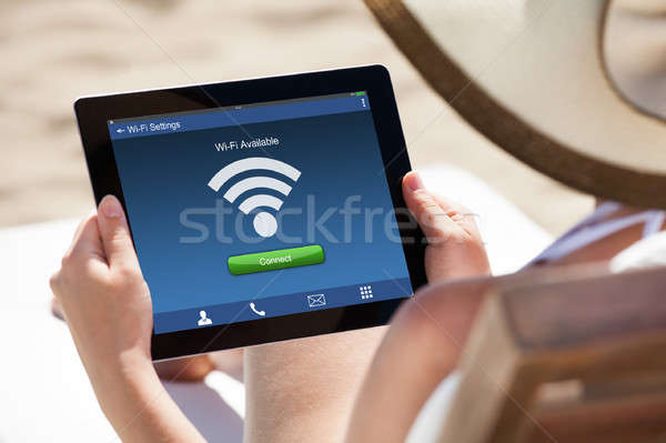 Woman Holding Digital Tablet At Beach Stock photo © AndreyPopov