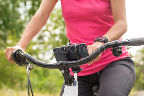 Female Cyclist Touching At Smart Phone On Bicycle Stock photo © AndreyPopov