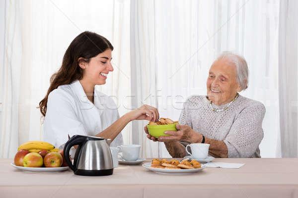 Mais velho mulher oferta enfermeira bolinhos Foto stock © AndreyPopov