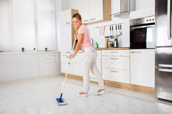 Woman With Mop Standing In The Kitchen Stock photo © AndreyPopov