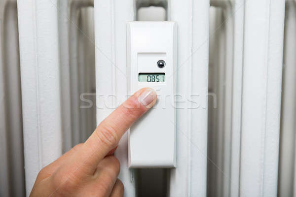 Woman Adjusting Temperature With Digital Thermostat Stock photo © AndreyPopov