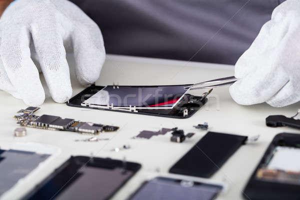 Repairman Disassembling Smartphone With Tweezers Stock photo © AndreyPopov