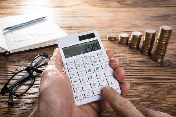 Person Calculating Profit On Calculator Stock photo © AndreyPopov