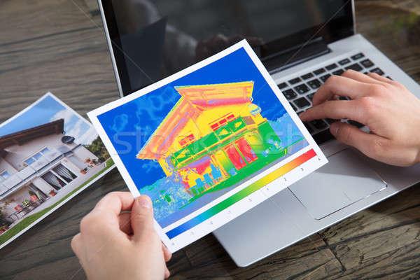 Personne chaleur perte maison utilisant un ordinateur portable Photo stock © AndreyPopov