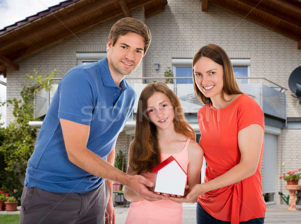 Stock photo: Daughter With Their Parents Holding House Model