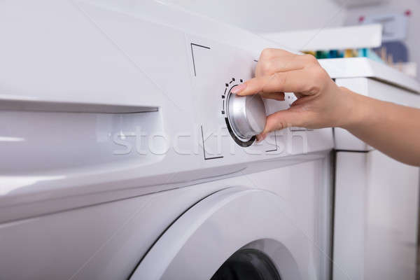 Woman Turning Button Of Washing Machine Stock photo © AndreyPopov