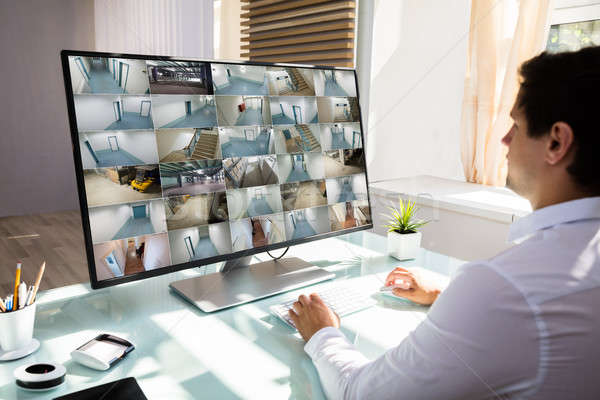 Businessman checking CCTV camera footage on computer Stock photo © AndreyPopov
