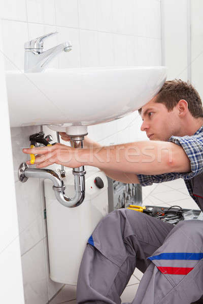 Young plumber fixing a sink in bathroom Stock photo © AndreyPopov
