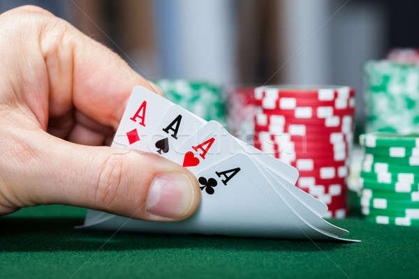 Poker player holding playing cards Stock photo © AndreyPopov