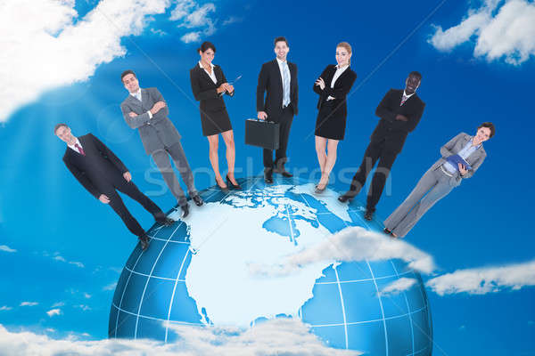 Confident Business People Standing On Globe Stock photo © AndreyPopov