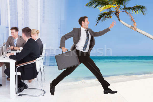 Businessman Escaping From Conference Meeting Towards Beach Stock photo © AndreyPopov