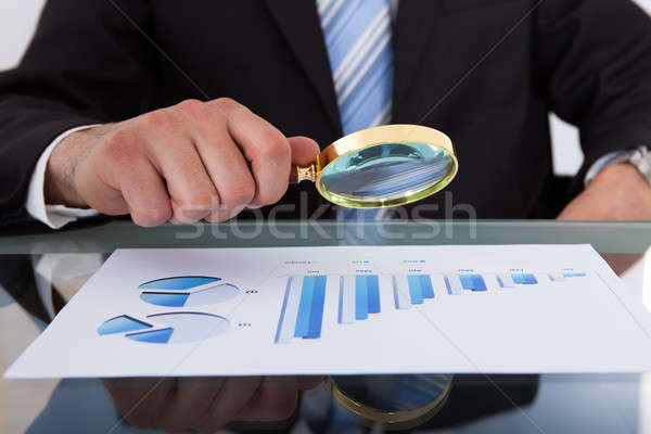 Businessman Analyzing Bar Graph Through Magnifying Glass Stock photo © AndreyPopov