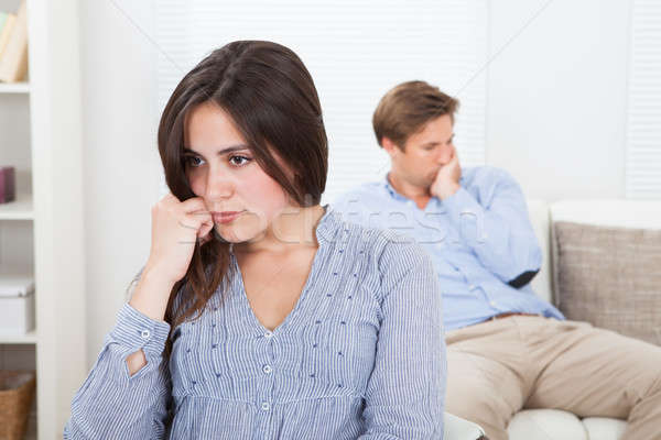 Upset Woman With Man Sitting On Sofa In Background Stock photo © AndreyPopov
