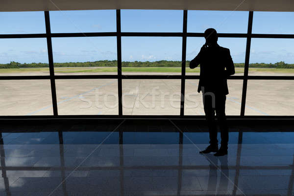 Businessman using mobile phone against airport window Stock photo © AndreyPopov