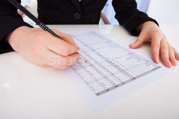 Businesswoman Writing On Financial Paper Stock photo © AndreyPopov