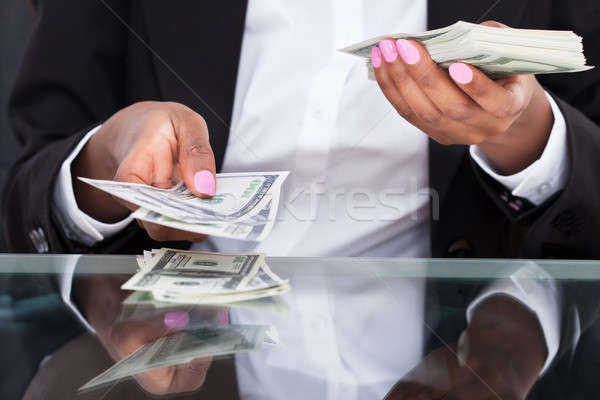 Businesswoman counting dollar bills at desk in office Stock photo © AndreyPopov