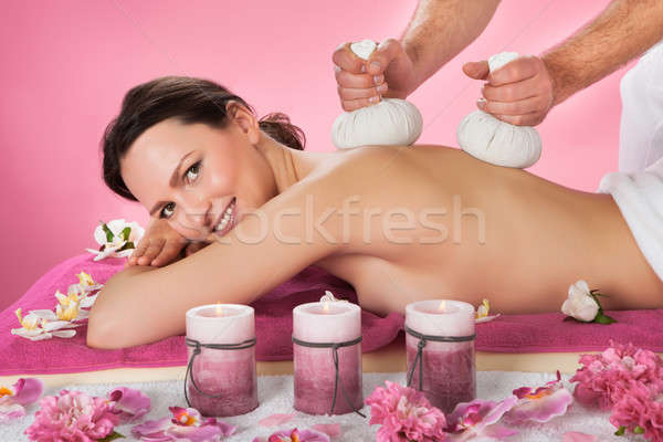Woman Receiving Herbal Massage With Balls In Spa Stock photo © AndreyPopov