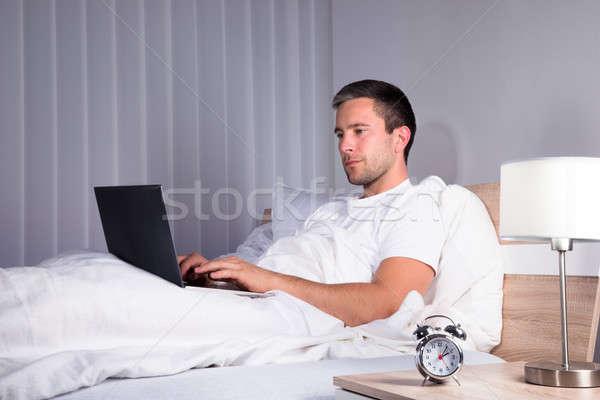 Man In Bedroom Using Laptop Stock photo © AndreyPopov