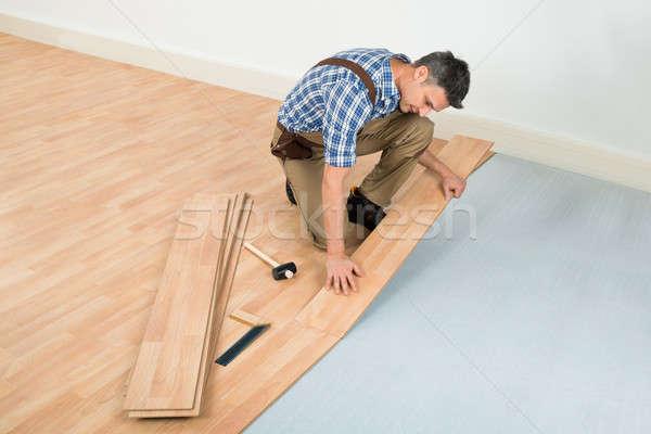 Man Installing New Laminated Wooden Floor Stock photo © AndreyPopov