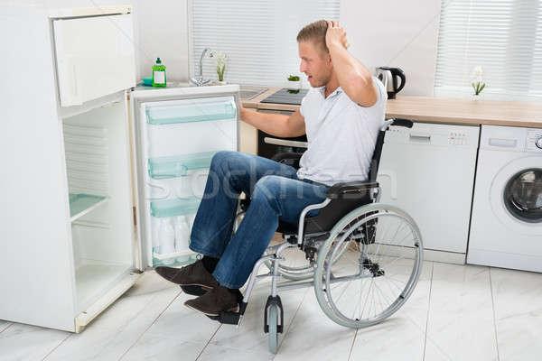 Stock fotó: Mozgássérült · férfi · néz · üres · hűtőszekrény · fiatalember