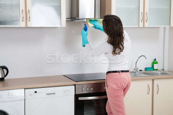 Femme nettoyage rag cuisine maison métal Photo stock © AndreyPopov