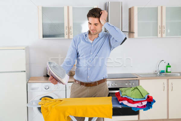 Man Ironing Clothes With Electric Iron Stock photo © AndreyPopov