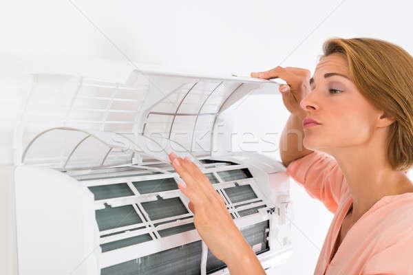 Femme ouverture climatiseur jeunes belle femme maison Photo stock © AndreyPopov