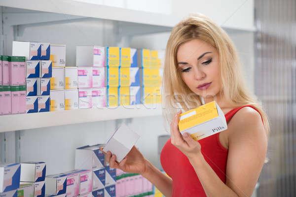 Beautiful Woman Examining Capsule Packet Stock photo © AndreyPopov