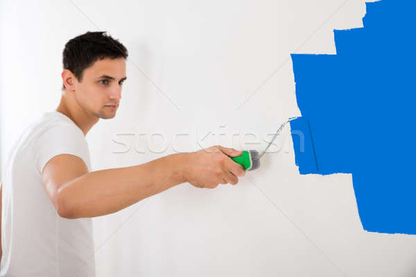Man Painting Wall With Blue Paint Roller Stock photo © AndreyPopov