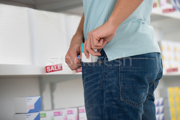 Shoplifter Putting Packet In Pocket Stock photo © AndreyPopov