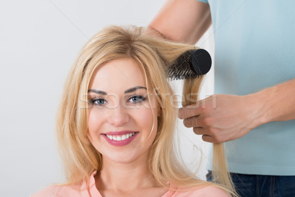 Hairstylist Brushing Woman's Hair At Salon Stock photo © AndreyPopov