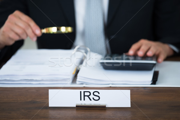 Auditor Examining Documents With Magnifying Glass At Table Stock photo © AndreyPopov