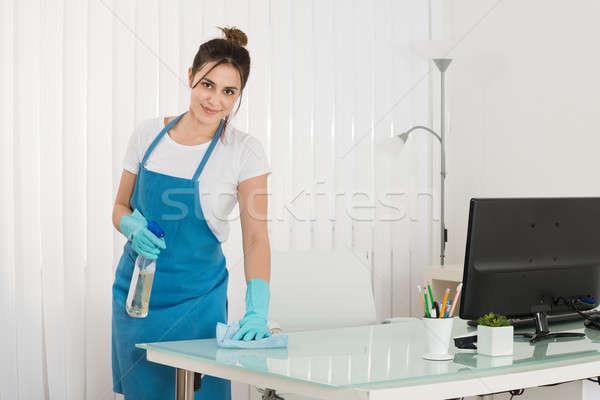 Genç kadın sprey silme büro Stok fotoğraf © AndreyPopov
