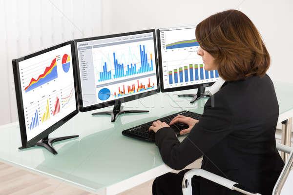 Femme d'affaires travail graphiques ordinateur jeunes bureau Photo stock © AndreyPopov