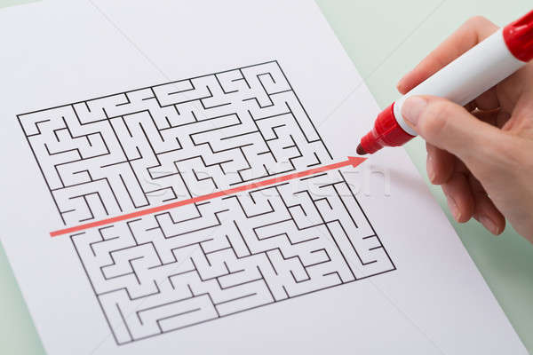 Woman Hand Drawing Straight Red Line Over Maze Stock photo © AndreyPopov