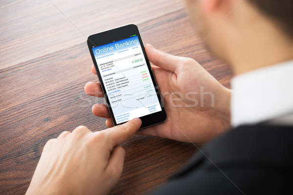 Businessman Doing Online Banking On Mobile Phone Stock photo © AndreyPopov