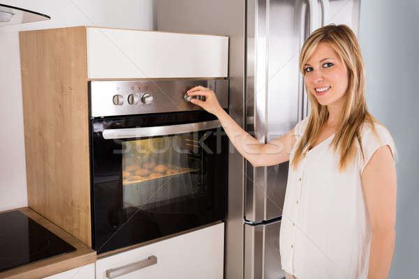 Woman Using Oven For Baking Cookies Stock photo © AndreyPopov