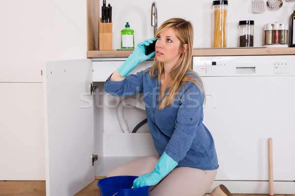 Woman Using Mobilephone Near Kitchen Sink Stock photo © AndreyPopov